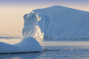 Sunlit iceberg and ice floe at dawn