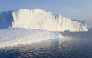 Sunlit iceberg and ice floe in deep blue waters
