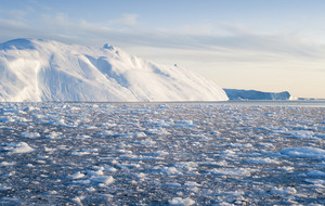 Sunlit iceberg and ice floe in icy waters at dawn