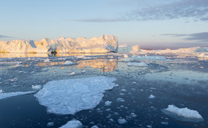 Sunlit iceberg and ice floes at dusk