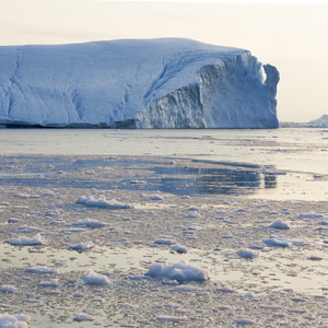 Sunlit iceberg and ice floes in icy waters at dusk