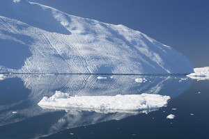 Sunlit iceberg and ice floes reflected in icy waters under a blue sky