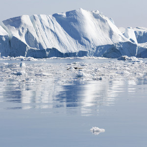 Sunlit iceberg and ice floes reflected in icy waters