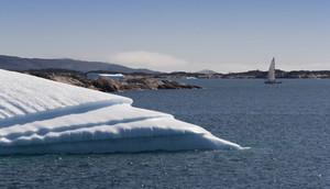 Sunlit iceberg and sailboat along the coast