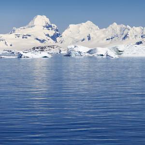 Sunlit iceberg and snowy coast