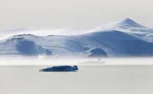 Sunlit iceberg floating in the water on a foggy day