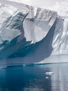 Sunlit iceberg in calm waters