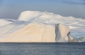 Sunlit iceberg in deep blue waters