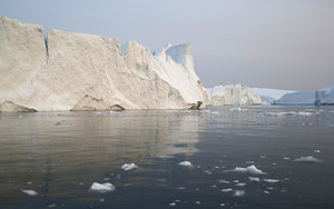 Sunlit iceberg in icy waters on a foggy day