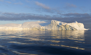Sunlit iceberg in rippling water