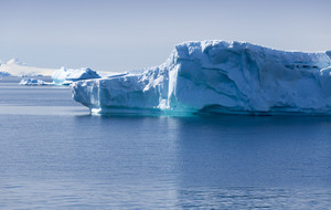 Sunlit iceberg in still waters