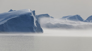 Sunlit iceberg on a foggy day