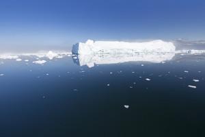 Sunlit iceberg reflected in dark water