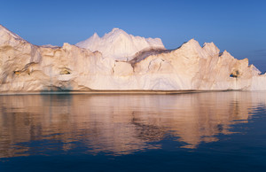 Sunlit iceberg reflected in rippling water