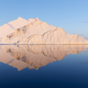 Sunlit iceberg reflected in still water at dawn