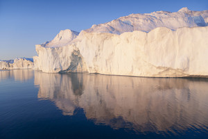 Sunlit iceberg reflected in the water