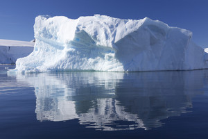 Sunlit iceberg reflected under a blue sky