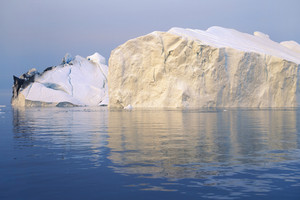 Sunlit iceberg streaked with dirt in deep blue water