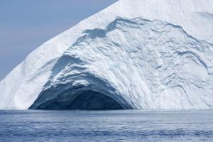Sunlit iceberg with a round crevasse under a blue sky