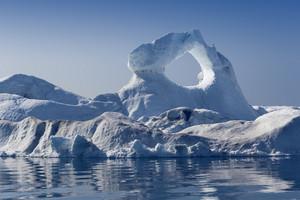 Sunlit iceberg with a unique hole structure against a blue sky
