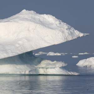 Sunlit iceberg with a unique ledge in icy waters