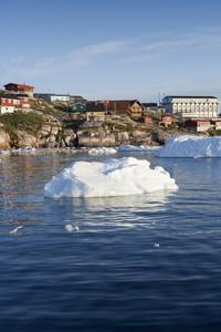 Sunlit icebergs along a coastal village