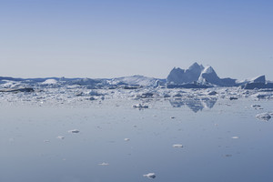 Sunlit icebergs and ice floe in icy water under a blue sky