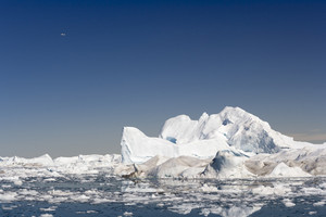 Sunlit icebergs and ice floe in icy waters with a plane overhead