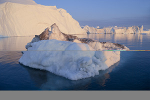 Sunlit icebergs and ice floe under a blue sky