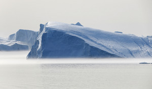 Sunlit icebergs floating in the water on a foggy day