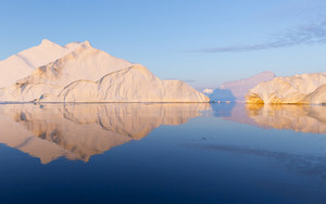 Sunlit icebergs reflected in clear water
