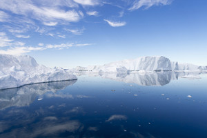 Sunlit icebergs reflected in still waters