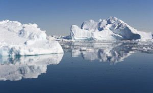 Sunlit icebergs reflected on the water under a blue sky
