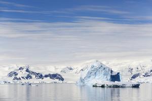 Sunlit icebergs under a cloudy sky