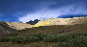 Sunlit mountains under a cloudy sky