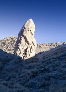 Sunlit rocks on a barren landscape under a blue sky