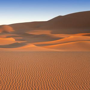 Sunlit sand dunes in the desert at dawn