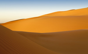 Sunlit sand dunes in the desert at sunrise
