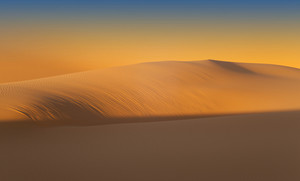 Sunlit sand dunes in the desert at sunset