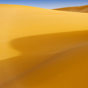 Sunlit sand dunes in the desert under a blue sky
