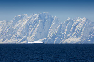 Sunlit, snowy coast and a small iceberg