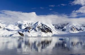 Sunlit, snowy coast reflected in still waters