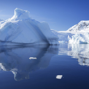 Sunlit, snowy iceberg and coast reflected in still waters