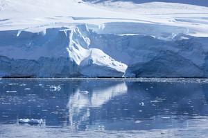 Sunlit, towering iceberg reflected in icy waters