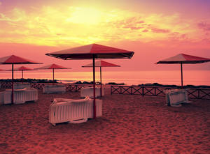 Sunrise over beach with parasols and recliners