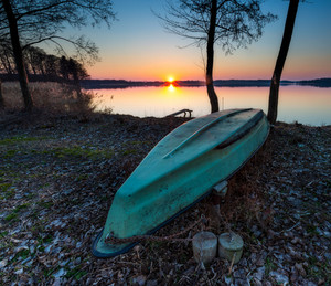 Sunset on lake shore with fisherman boats out of water. Tranquil scene photographed in Poland.