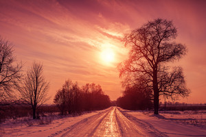 Sunset over snowy road