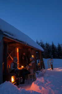 Sunset winter cottage friends enjoying evening in snow countryside