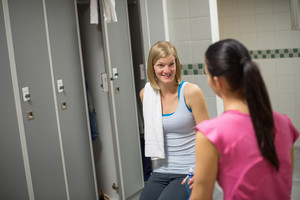 Surprised woman talking with friend in changing room at healthclub