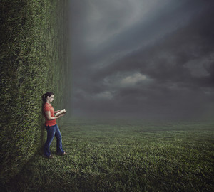 Surreal image of a grassy landscape with a woman reading a book.